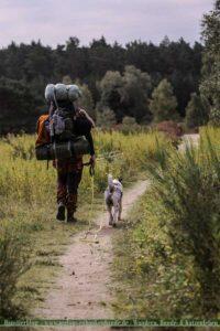Hund wandert mit Mensch auf einem Fernweg